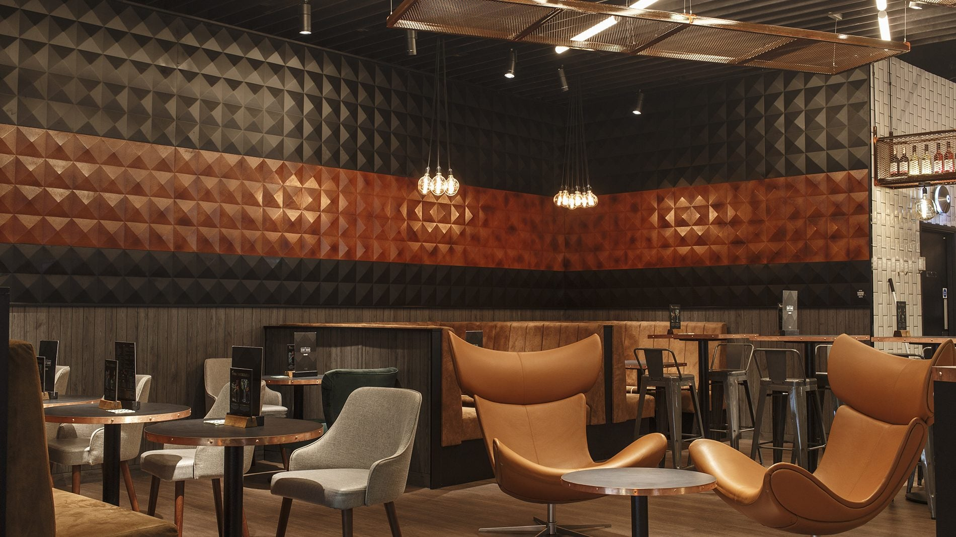 Seating area with 3D pyramid wall panelling at The Edit Bar designed for Vue
