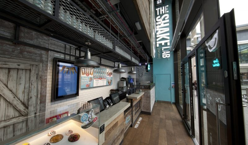 Interior design of the milkshake parlour The Shake Lab with counter and illuminated logo sign