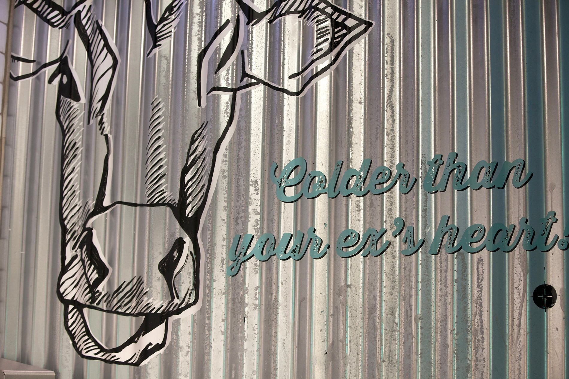 Corrugated metal with cow graphic and slogan 'colder than your ex's heart'