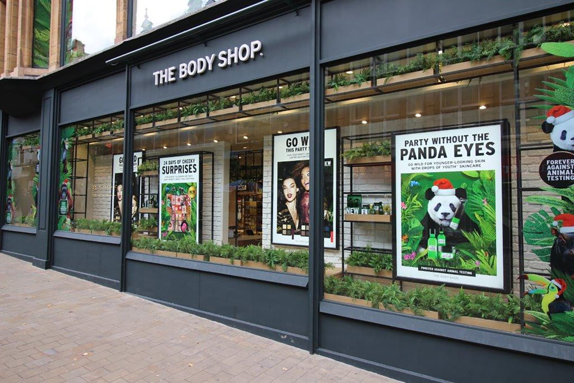 exterior of the body shop store with 'party without the panda eyes' window display