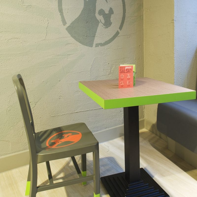 table and chair in restaurant with donkey graphic on the wall