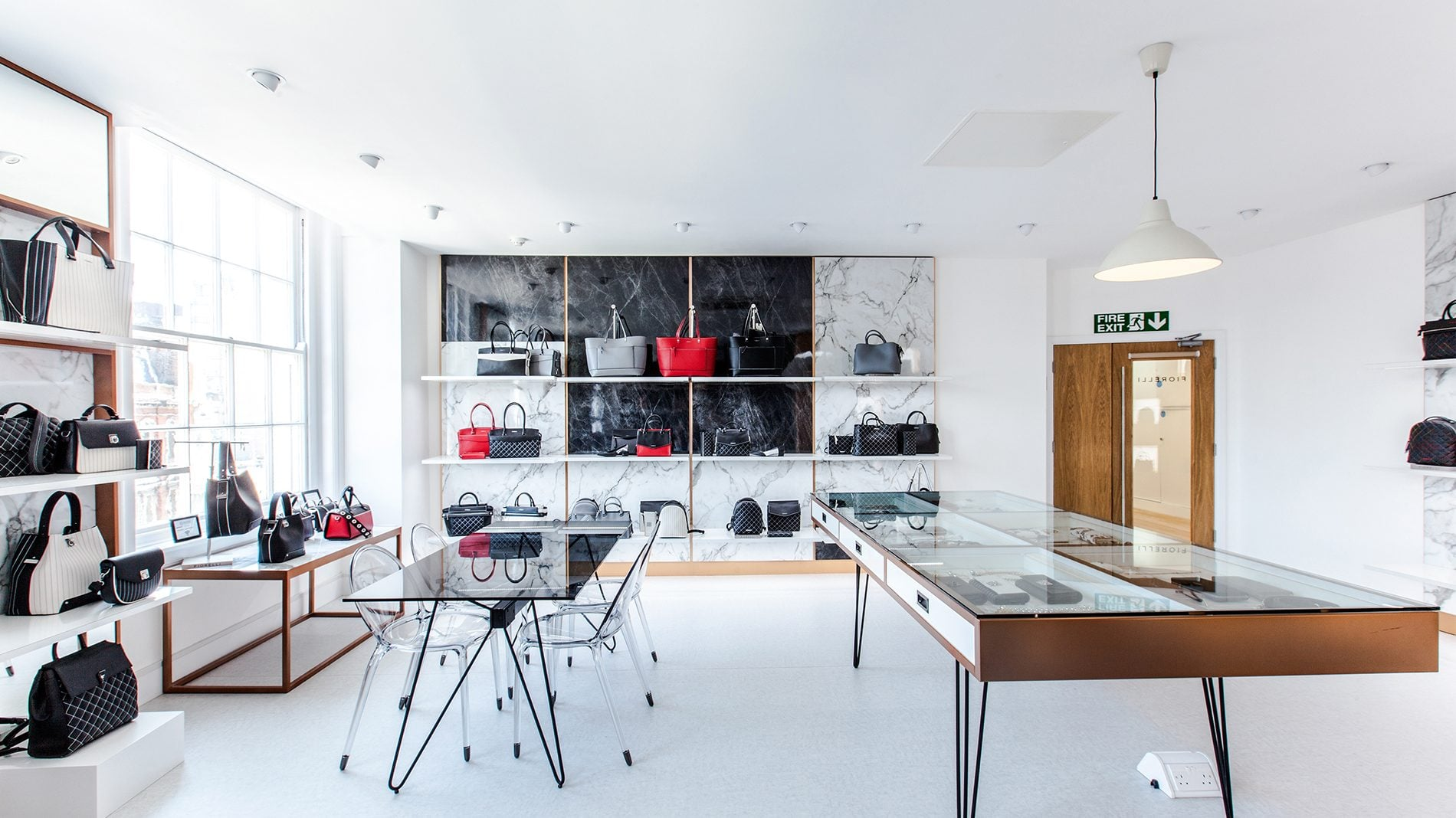 Fiorelli show room with shelves of handbags and a display table