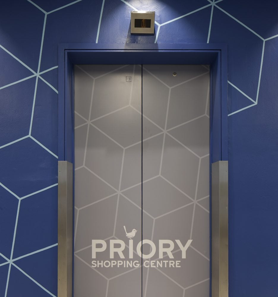 Graphics on escalator doors at Priory shopping centre