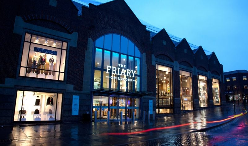The Friary shopping centre exterior view at nighttime with signage illuminated