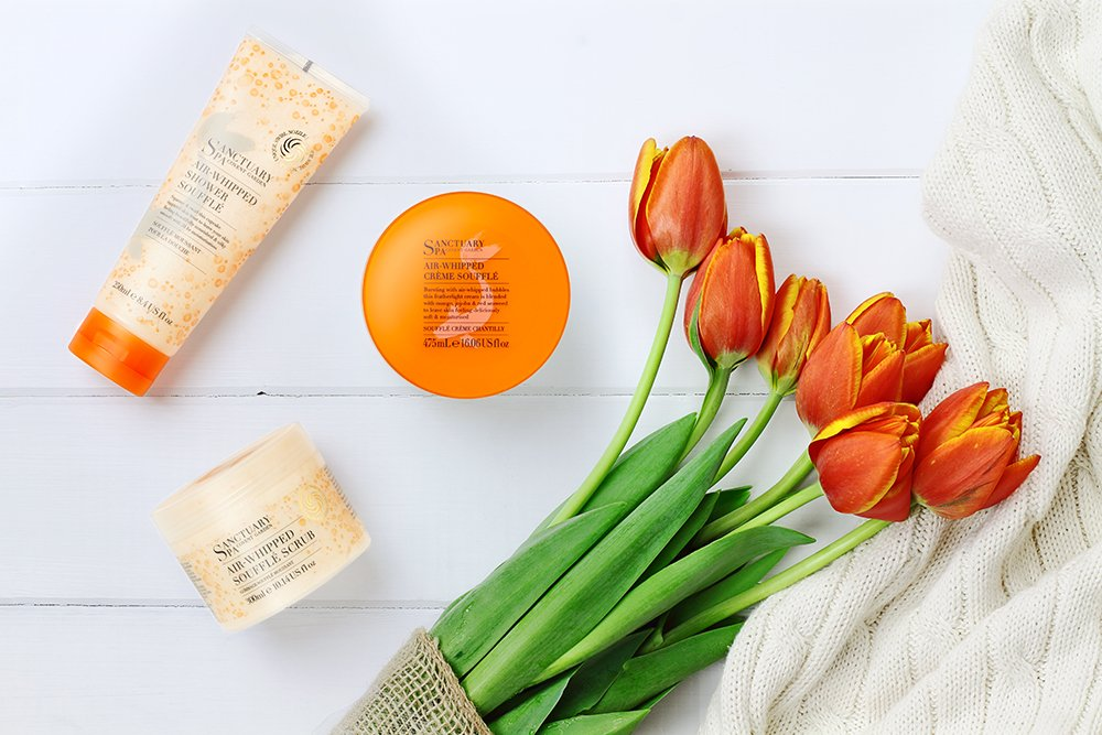 flat lay of sanctuary spa bodycare with flowers