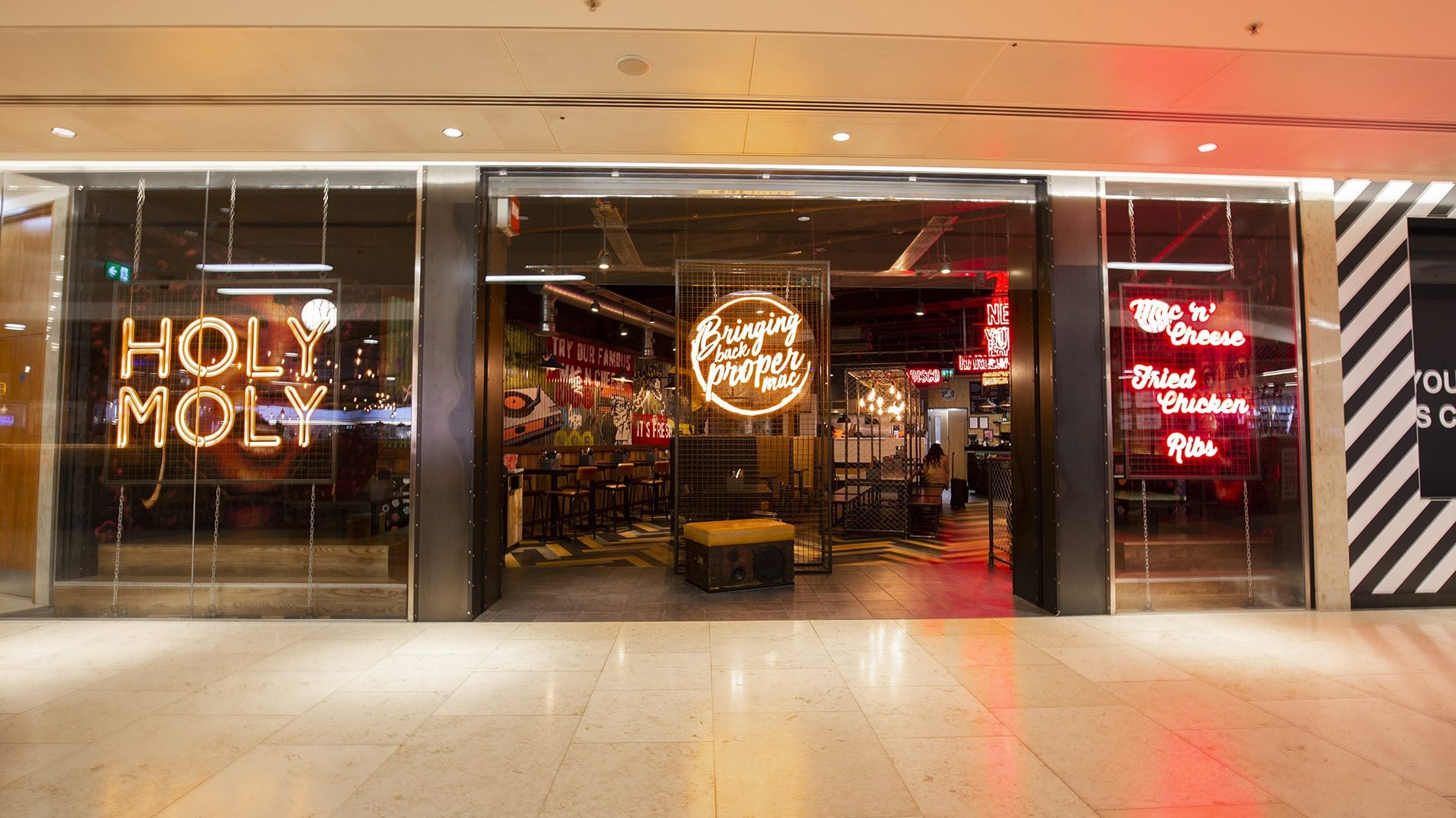 Store front of Holy Moly with illuminated signs