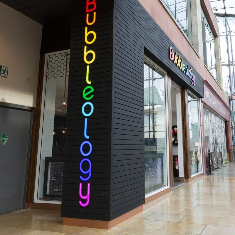 Side view of Bubbleology store front with illuminated sign