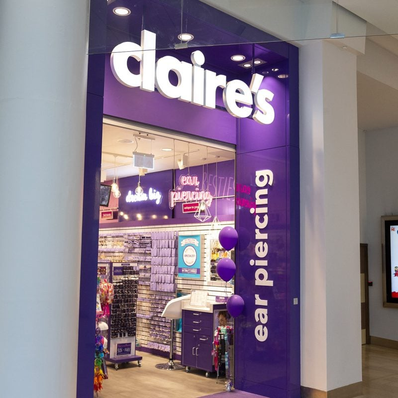Claire's store front with side view graphics reading ear piercing